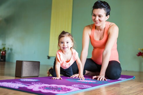 Mixed Race expectant mother and daughter on exercise mat - BLEF01282