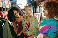 Friends laughing in retail store on bus - BLEF01387