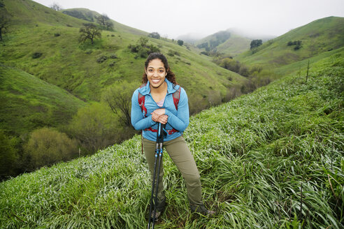 Smiling mixed race woman hiking with walking sticks - BLEF01402