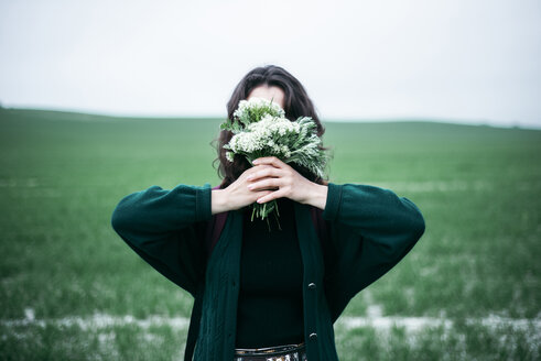 Caucasian woman holding wildflowers in front of face - BLEF01516