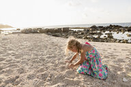 Caucasian girl playing in sand at beach - BLEF01588