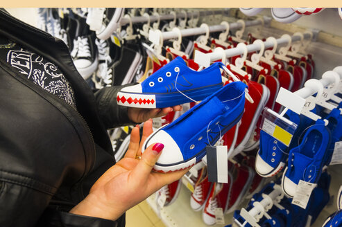 Hands of Caucasian woman holding sneakers in store - BLEF01597