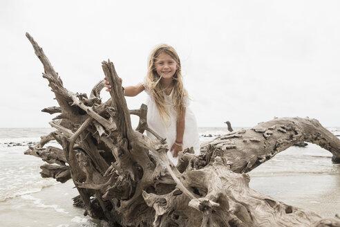 Caucasian girl posing on driftwood on beach - BLEF01651