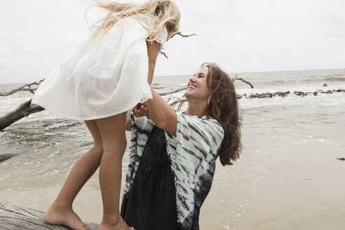 Caucasian mother and daughter playing on driftwood on beach - BLEF01654