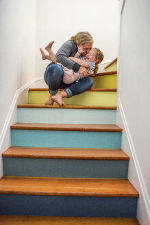 Caucasian mother kissing daughter on staircase - BLEF01663