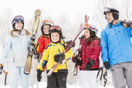 Smiling Caucasian family carrying skis in snow - BLEF01669