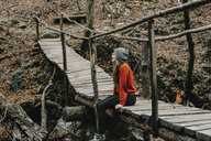 Caucasian woman sitting on footbridge in woods - BLEF01723