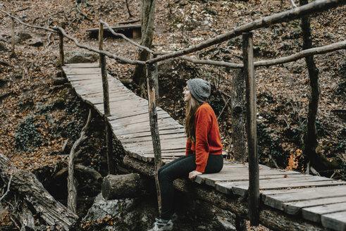 Caucasian woman sitting on footbridge in woods - BLEF01723