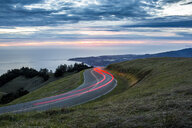 Light trails on winding road near ocean - BLEF01747