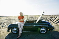 Older Caucasian woman leaning on convertible car with surfboard on beach - BLEF01753