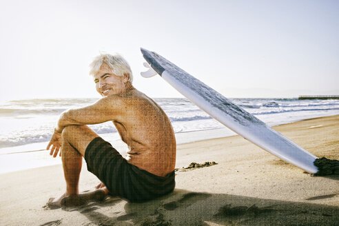 Older Caucasian man sitting on beach with surfboard - BLEF01756