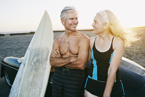 Older Caucasian couple leaning on convertible car with surfboards - BLEF01759