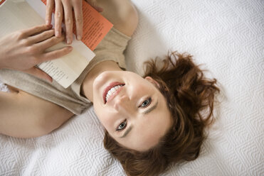 Caucasian woman laying on bed reading book - BLEF01798