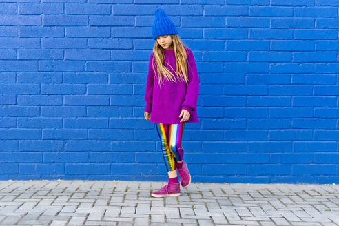 Portrait of girl wearing blue cap and oversized pink pullover standing in front of blue wall looking down - ERRF01196