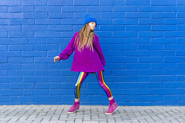 Portrait of girl wearing blue cap and oversized pink pullover standing in front of blue wall dancing - ERRF01199