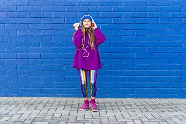 Girl wearing blue cap and oversized pink pullover standing in front of blue wall listening music with headphones - ERRF01202
