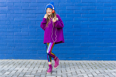 Singing girl dancing in front of blue wall while listening music with headphones - ERRF01205