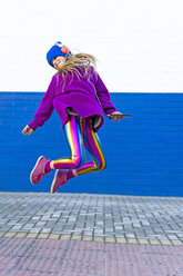 Happy girl with headphones and smartphone jumping in the air - ERRF01208