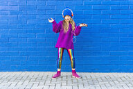 Singing girl wearing oversized pink pullover listening music with headphones in front of blue wall - ERRF01211