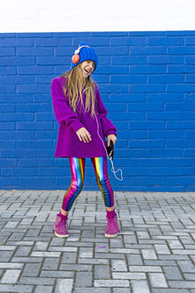 Singing and dancing girl listening music with headphones in front of blue wall - ERRF01214