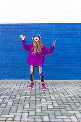 Singing girl listening music with headphones in front of blue wall - ERRF01217