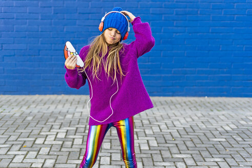 Portrait of girl dancing outdoors while listening music with headphones and smartphone - ERRF01220