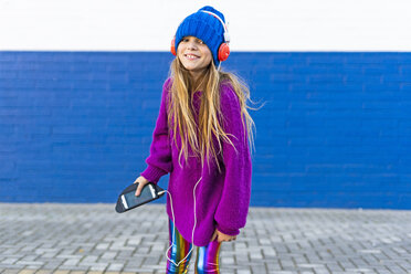 Portrait of happy girl listening music with headphones and smartphone - ERRF01223