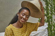 Portrait of happy woman putting on a traditional hat - VEGF00107