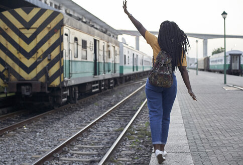 Rear view of young woman at the edge of the rail at the train station - VEGF00116