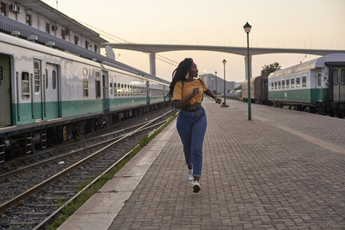 Young woman running on platform at the train station - VEGF00119