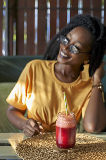 Smiling young woman with dreadlocks having a smoothie in a cafe - VEGF00122