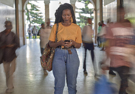 Young woman at the train station checking her phone while people passing by - VEGF00131