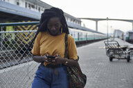 Young woman on platform at the train station checking her phone - VEGF00134