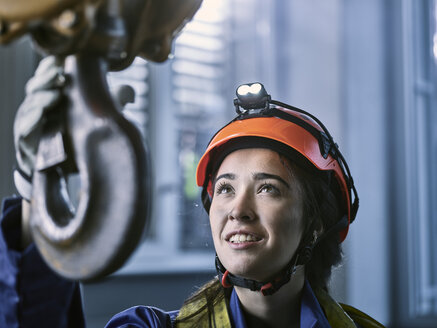 Young female industrial worker with safety helmet taking hook of indoor crane - CVF01125