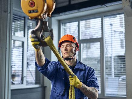 Industrial worker fixing hoist sling on indoor crane - CVF01128