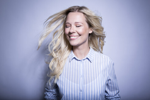 Portrait of happy blond woman tossing her hair - MFRF01291