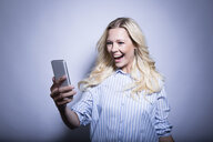 Portrait of happy blond woman looking at smartphone - MFRF01294