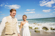Caucasian bride and groom holding hands on beach - BLEF01853