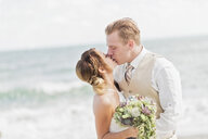 Caucasian bride and groom kissing on beach - BLEF01856