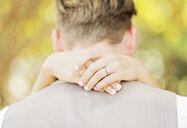 Hands of Caucasian bride hugging groom outdoors - BLEF01859