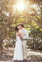 Caucasian bride and groom kissing under trees - BLEF01862