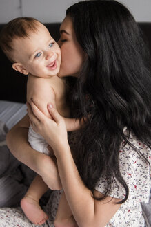 Caucasian mother kissing baby son in bed - BLEF01895