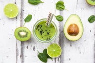 Glass of green smoothie with avocado, spinach, kiwi and lime - LVF07997