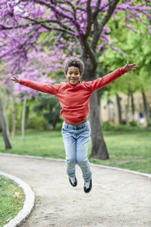 Spain, Madrid, Madrid. Happy black boy, seven years old, jumping outdoors raising arms in an urban park. Lifestyle concept. - JSMF01047