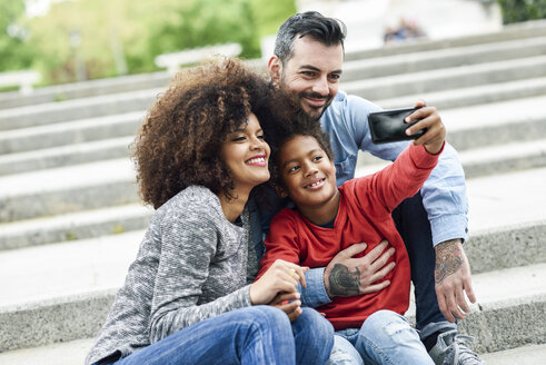 Happy family taking selfies in a park - JSMF01059