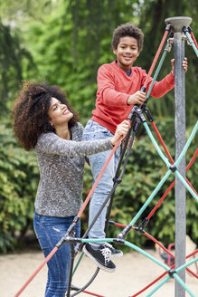 Mother and son playing on playground in a park, climbing in a jungle gym - JSMF01062