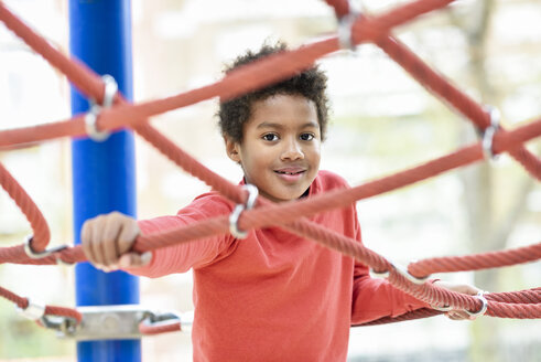 Spain, Madrid, Madrid. Happy black boy, seven years old, playing outdoors in an urban park playground. Lifestyle concept. - JSMF01065