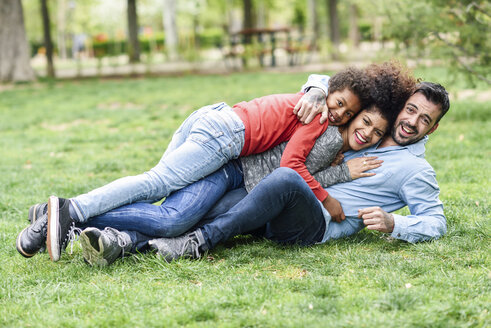 Happy family embracing, lying on grass in a park - JSMF01068
