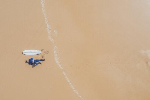 Portugal, Algarve, Sagres, Praia da Mareta, ein junger Mann liegt mit Surfboard am Strand, Surfen an der Algarve, Luftaufnahme, Drohnenaufnahme, Vogelperspektive - MMAF00899