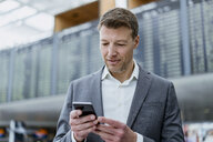 Portrait of businessman using cell phone at the airport - DIGF06839
